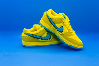 yellow nike athletic shoes on white surface shoe zoom background