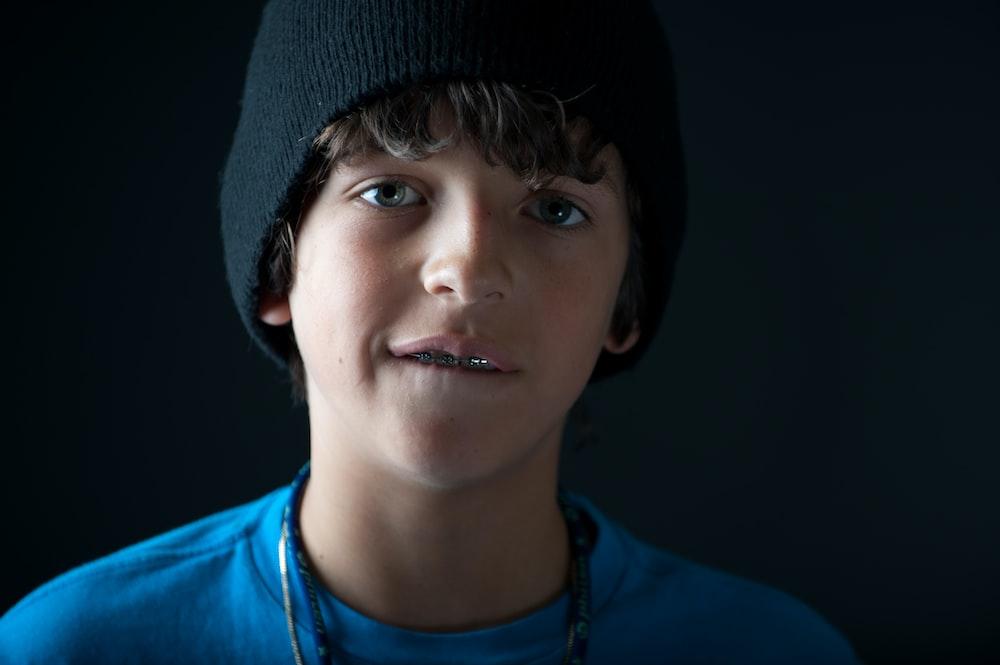 boy in blue crew neck shirt wearing black knit cap