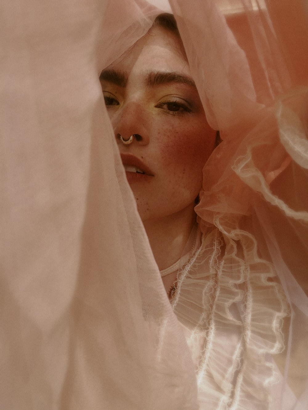woman in white veil covering her face with white sheer textile