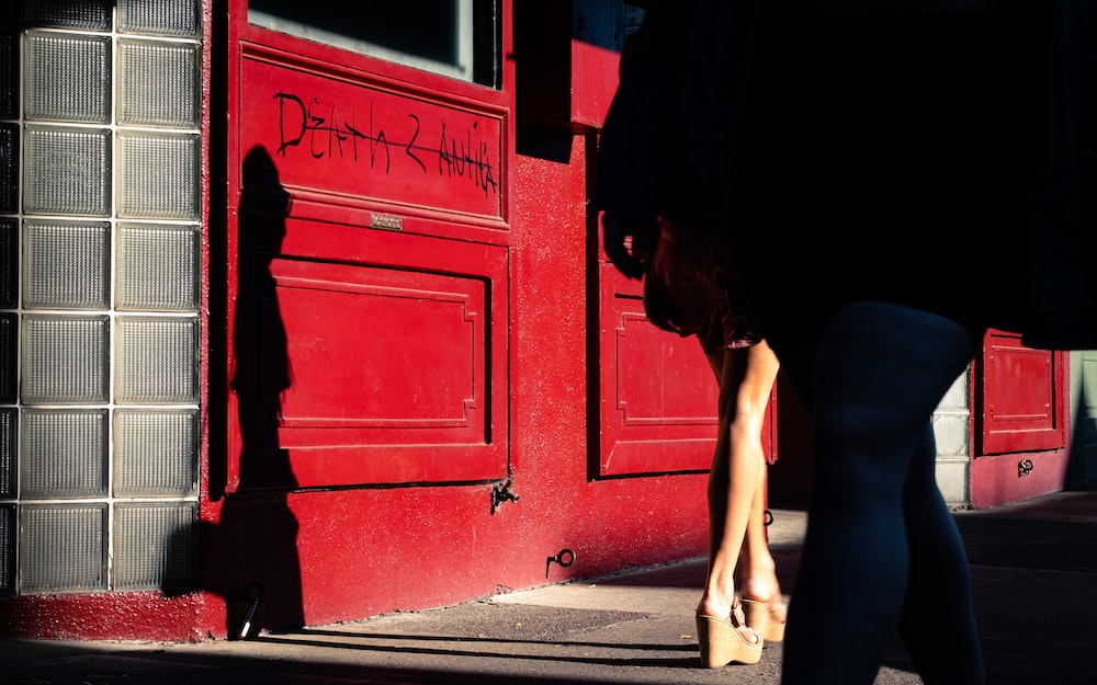 woman in black tank top and black shorts leaning on red wooden door