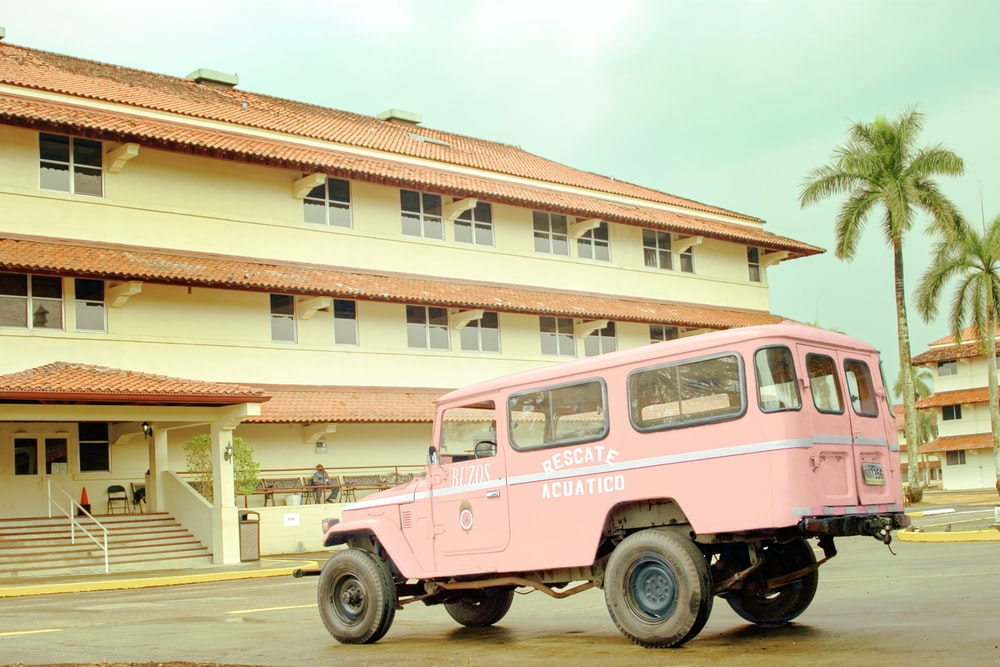 pink and white vintage car parked in front of white and brown concrete building during daytime