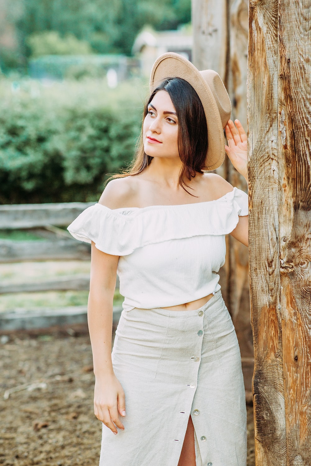 woman in white shirt leaning on brown wooden post during daytime