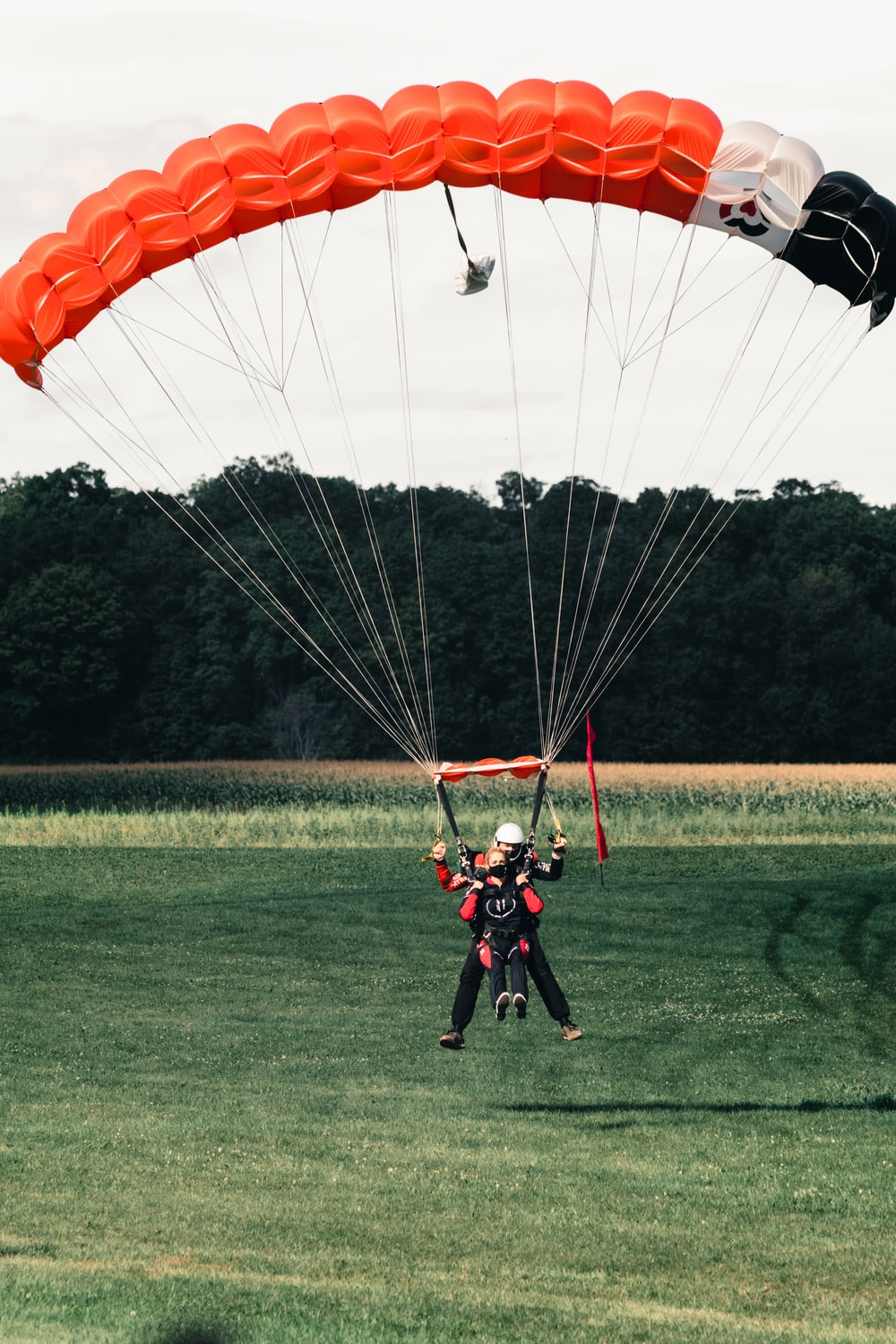 2 men in red and black suit riding on yellow and red parachute