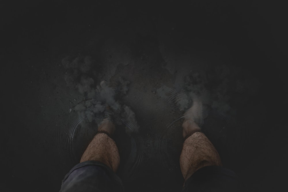 person in black shorts standing on black floor