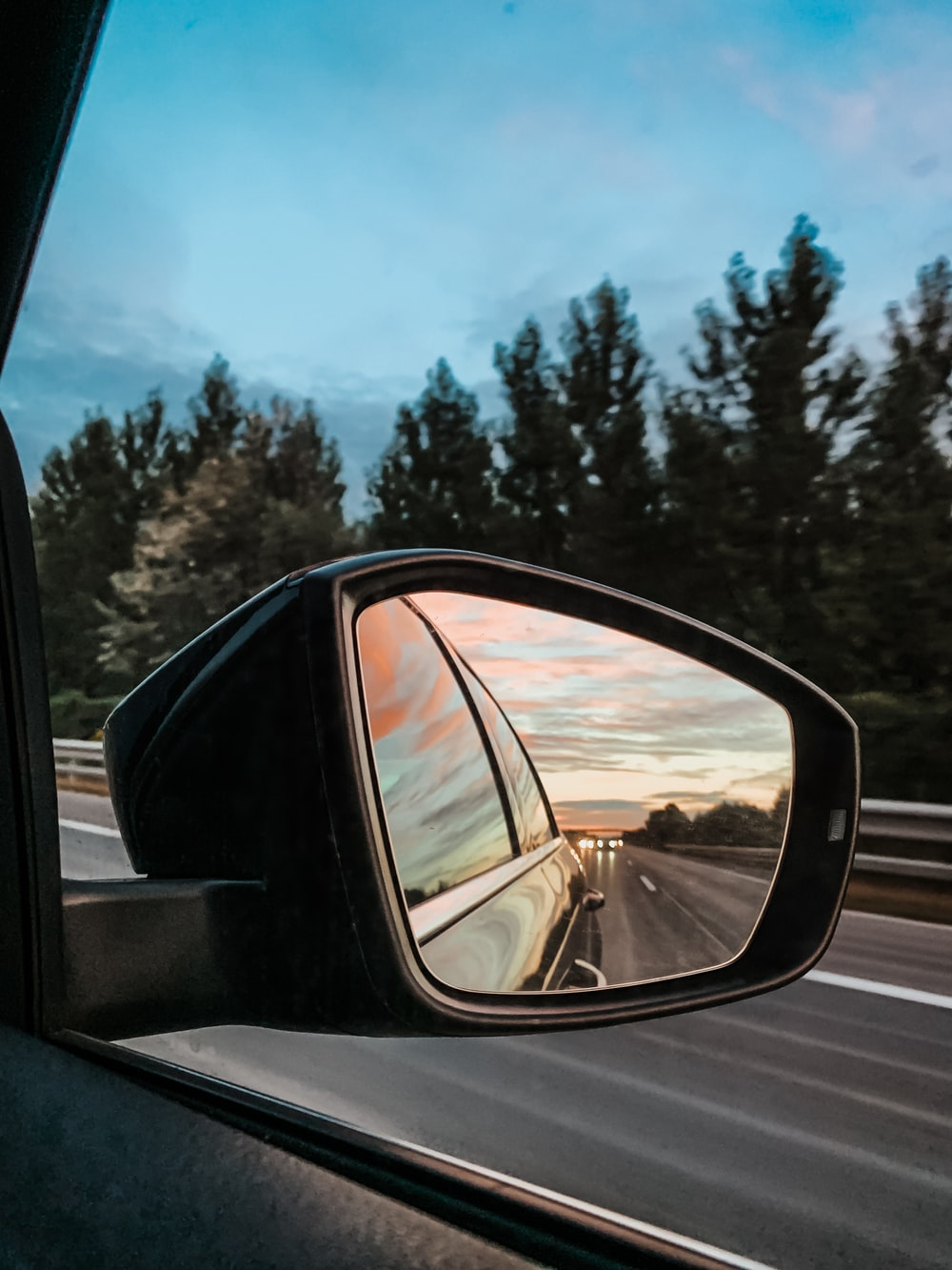 car side mirror showing car on road during daytime