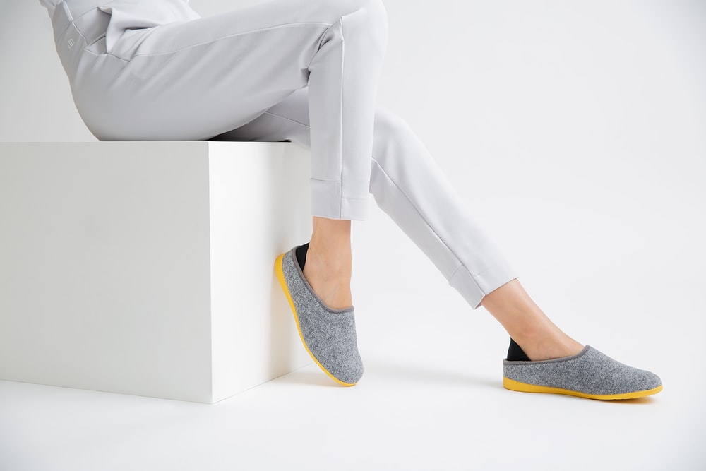 person in gray pants wearing blue and yellow flats