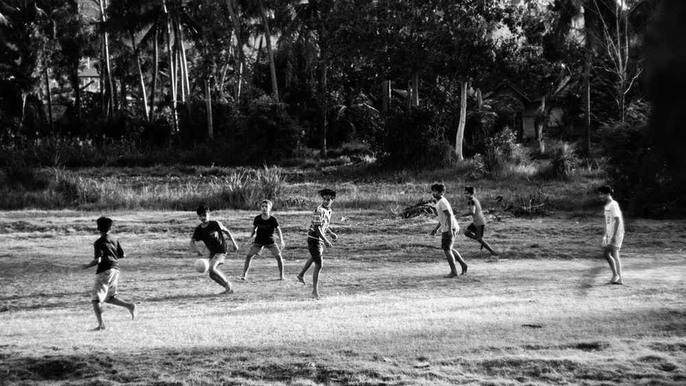 grayscale photo of children playing on field