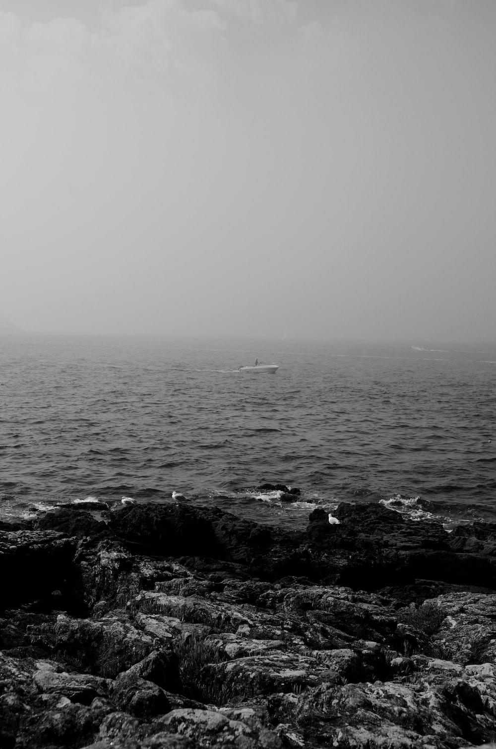 black rocks on body of water