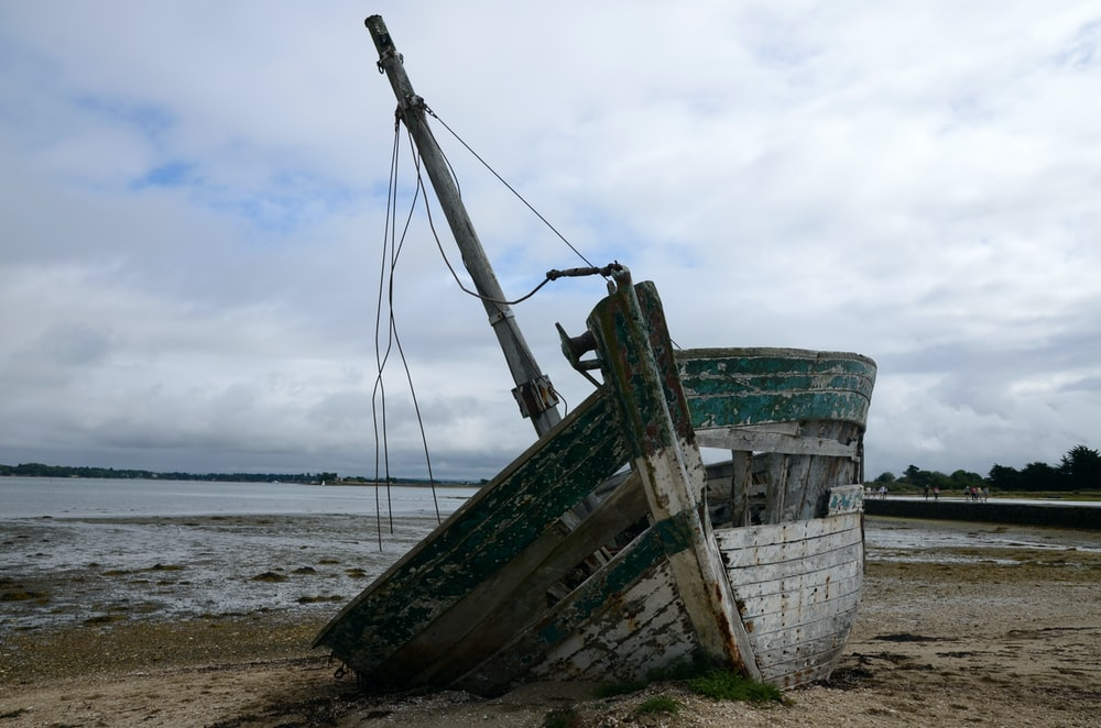 green and white boat on beach during daytime