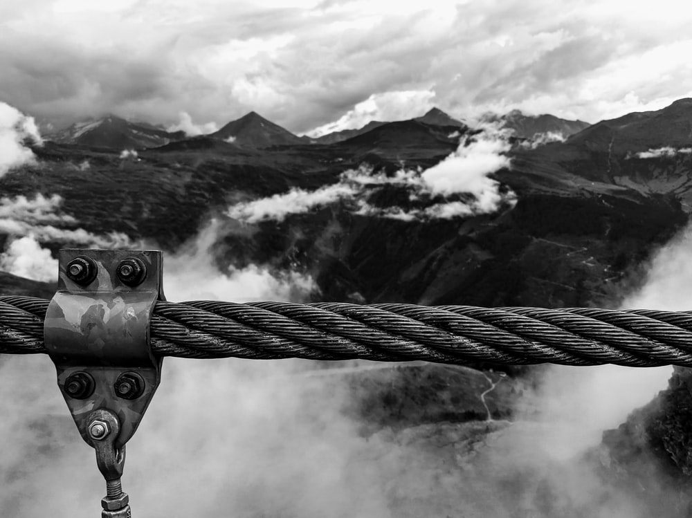 grayscale photo of rope with mountain range in distance