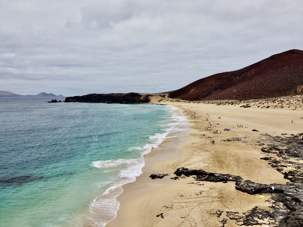 brown sand beach with green water waves under white clouds and blue sky during daytime