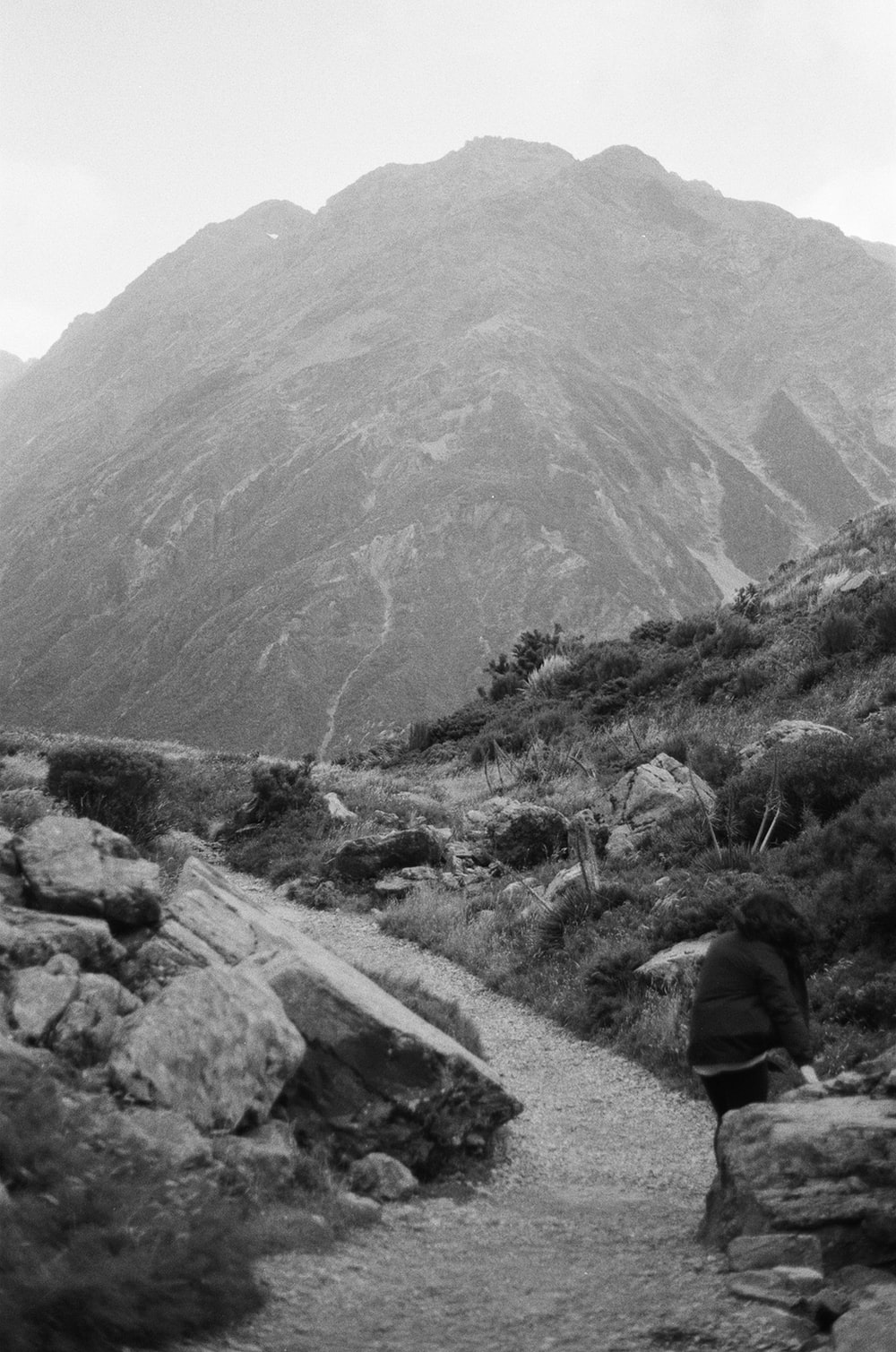 grayscale photo of person sitting on rock near mountain