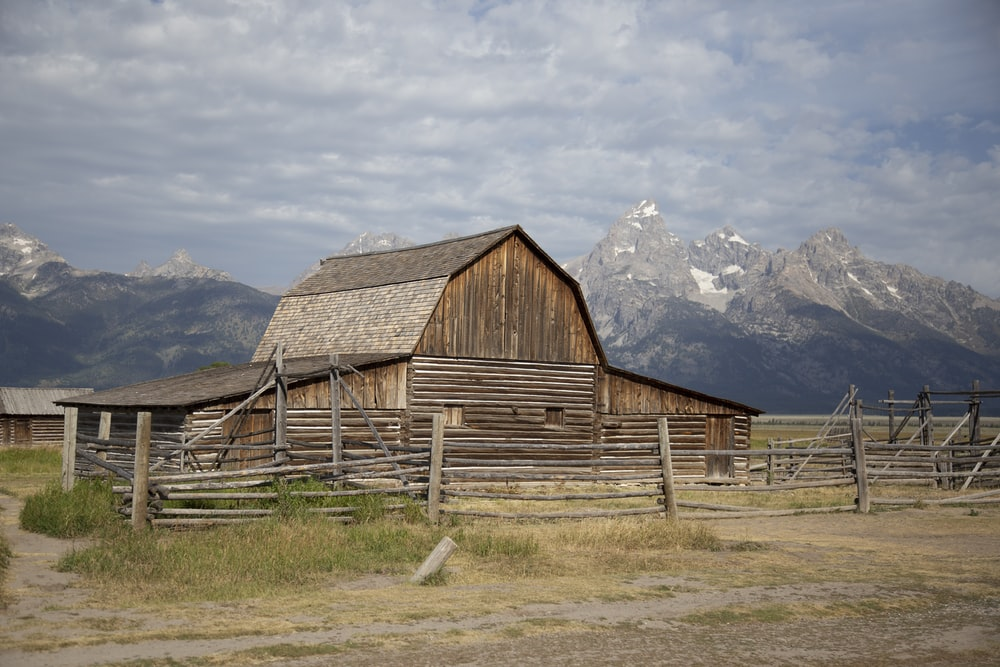 brown wooden barn on green grass field near mountains under white clouds during daytime