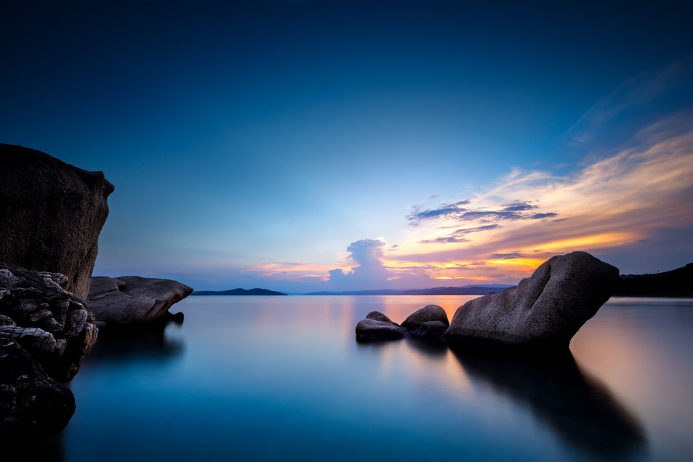 gray rock formation on body of water during sunset