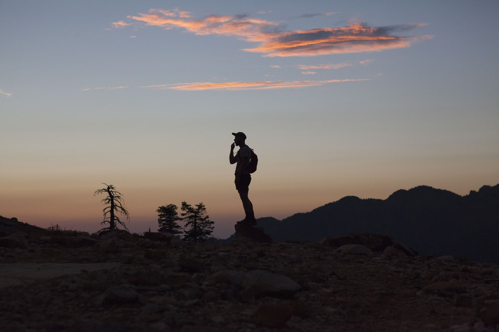 silhouette of man standing on rocky ground during sunset