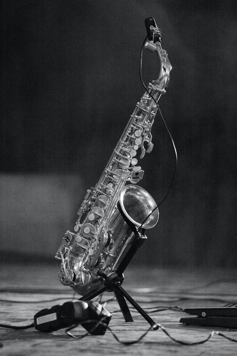 grayscale photo of saxophone on floor