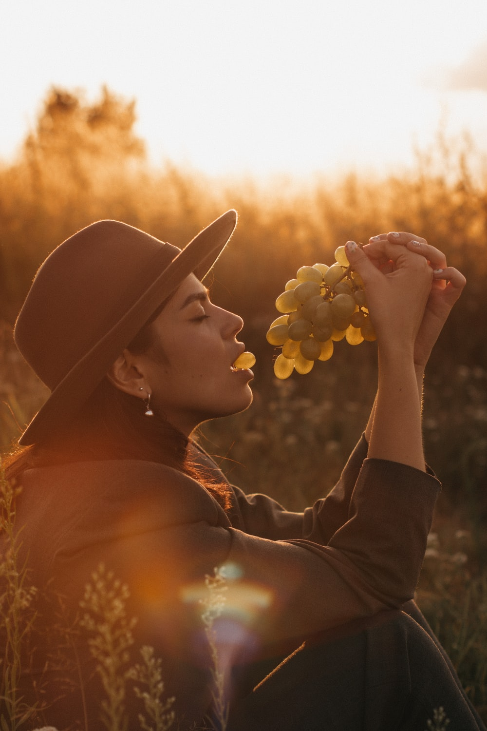 woman in black hat holding white flowers