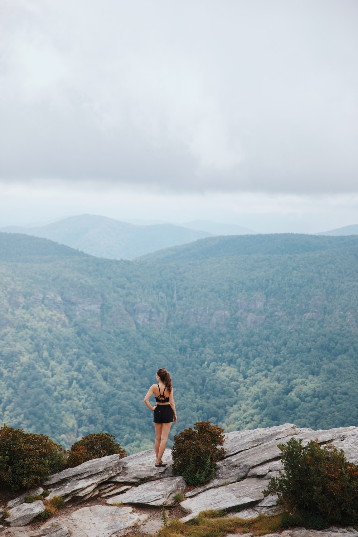 woman in black tank top sitting on rock during daytime