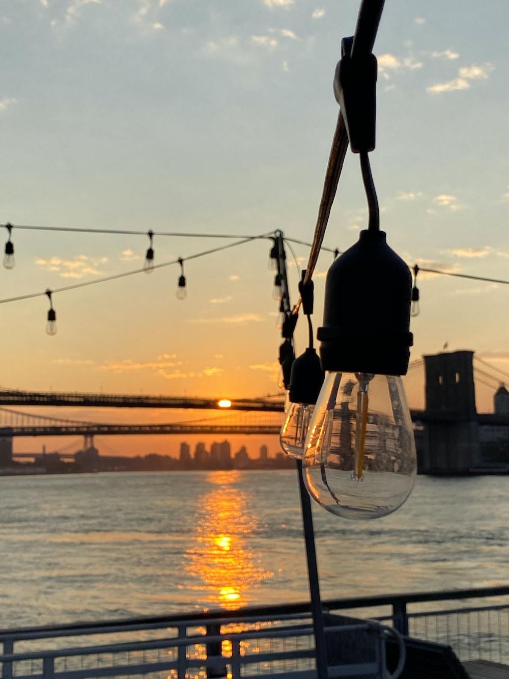 black light post near body of water during sunset