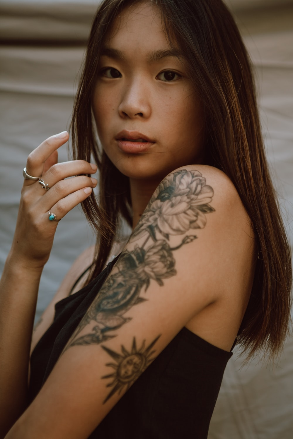 woman with black floral tattoo on her left arm