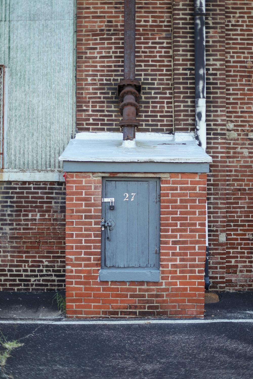 brown brick wall with black wooden door