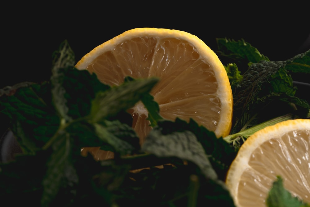 sliced orange fruit on green leaves