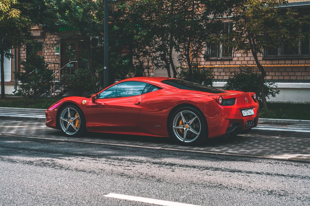 red ferrari 458 italia parked on road side during daytime