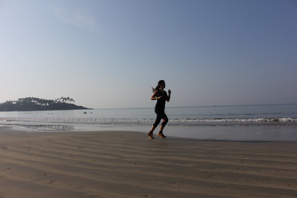 woman in black dress running on beach during daytime
