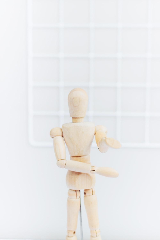 brown wooden human figurine on white background