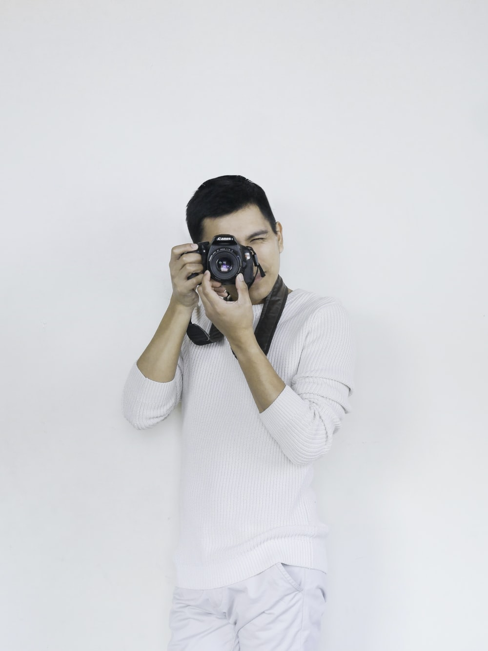 woman in white sweater holding black dslr camera