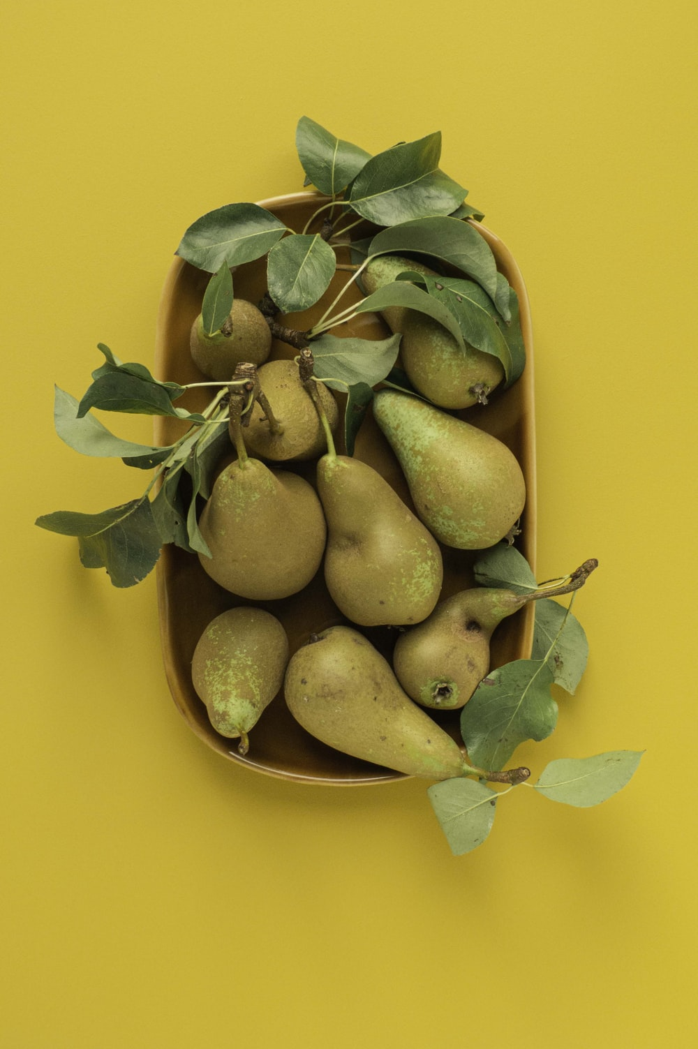 green and yellow fruits on yellow round plate