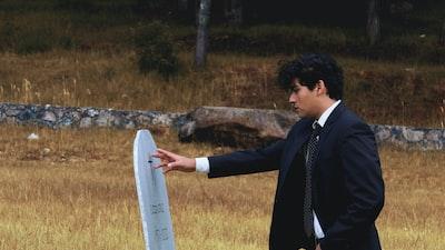 man in black suit holding white surfboard pueblo revival zoom background