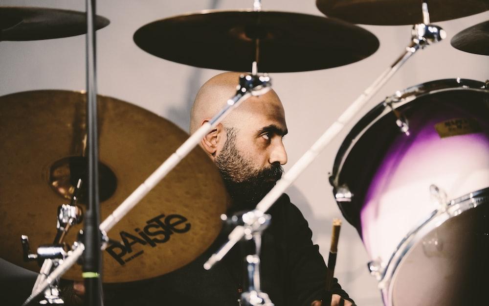 man in black jacket playing drum