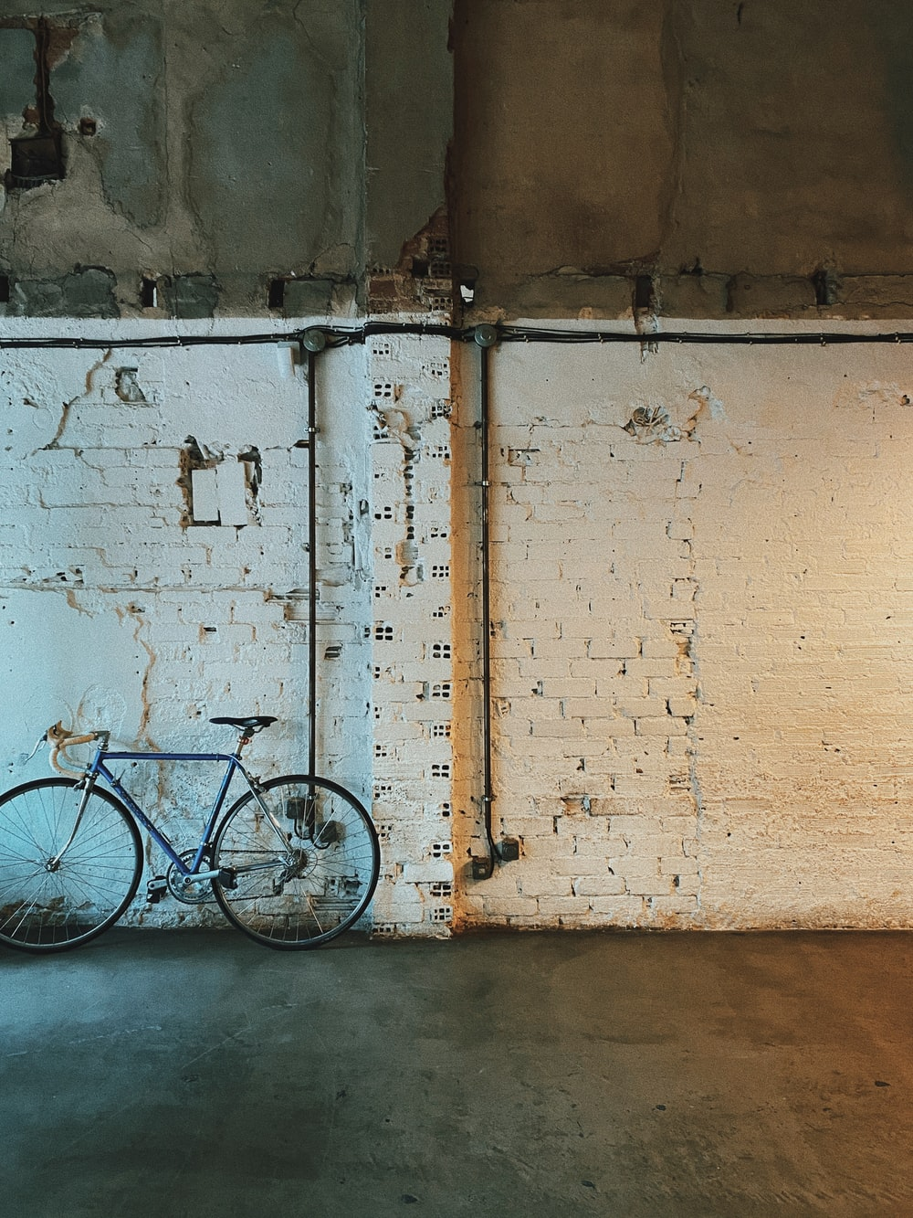 blue city bike leaning on white wall