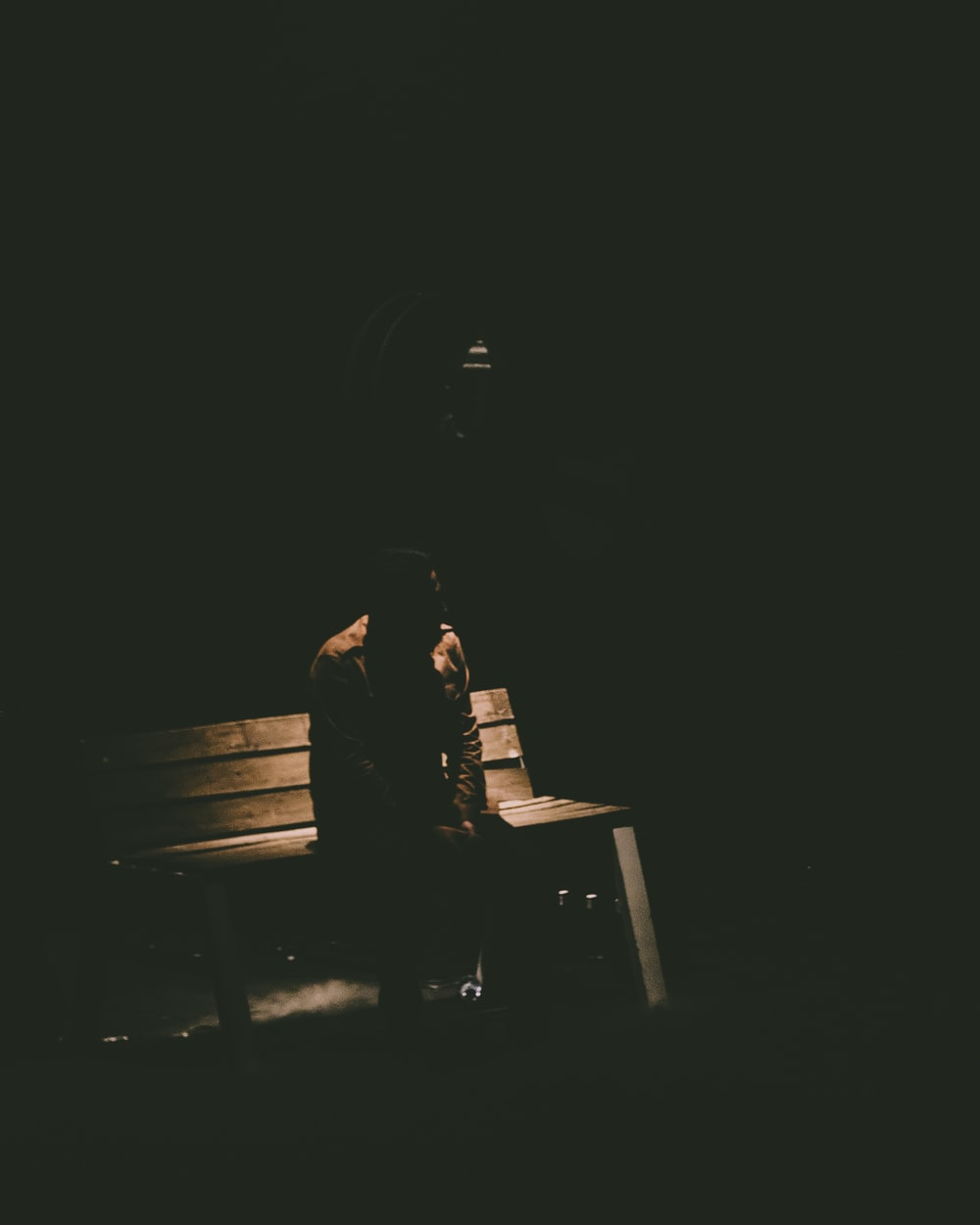 person sitting on bench in dark room