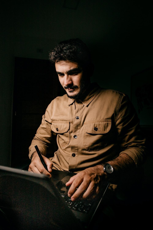 man in brown dress shirt holding black smartphone