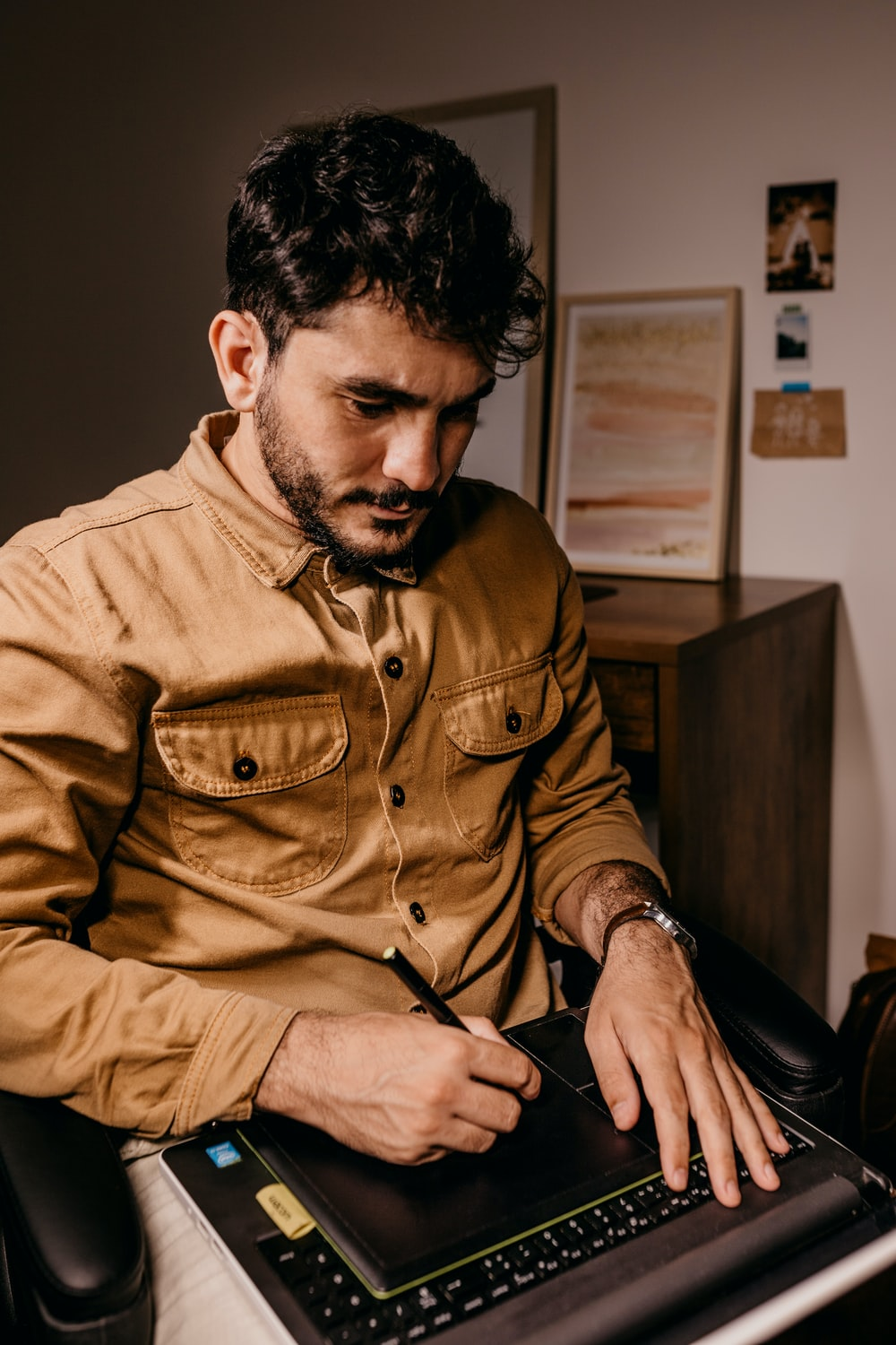 man in brown button up long sleeve shirt holding black smartphone