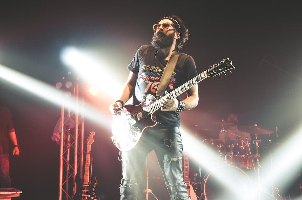 man in black crew neck t-shirt playing electric guitar