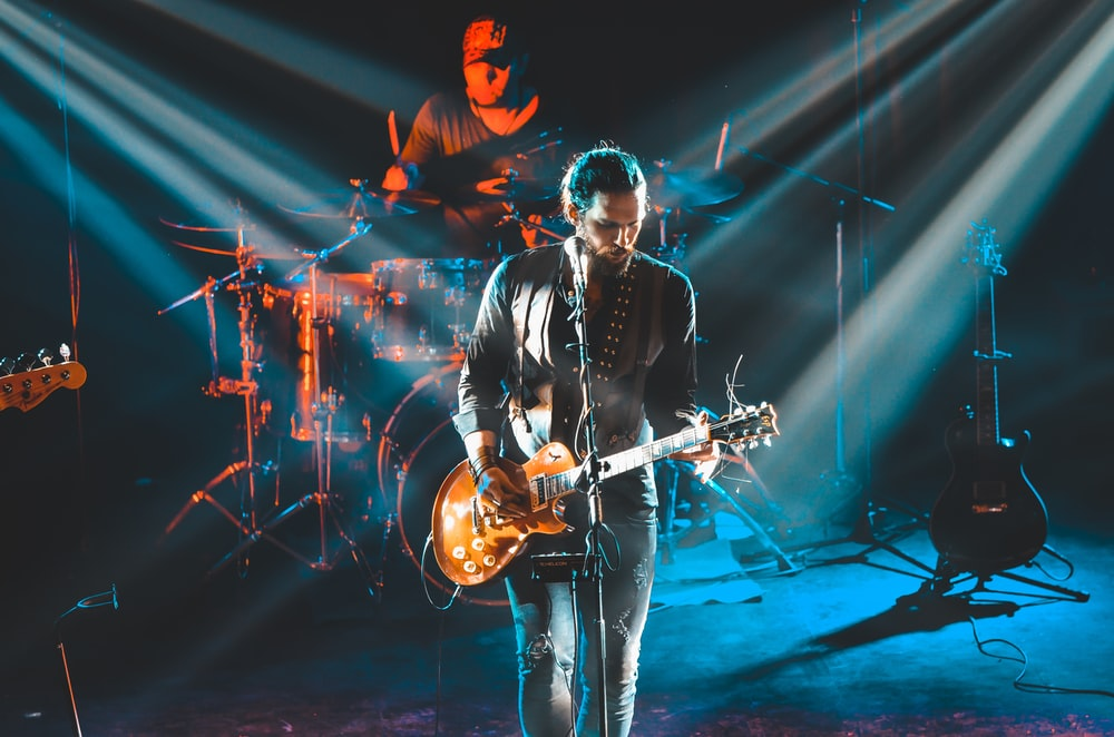 man in black leather jacket playing guitar