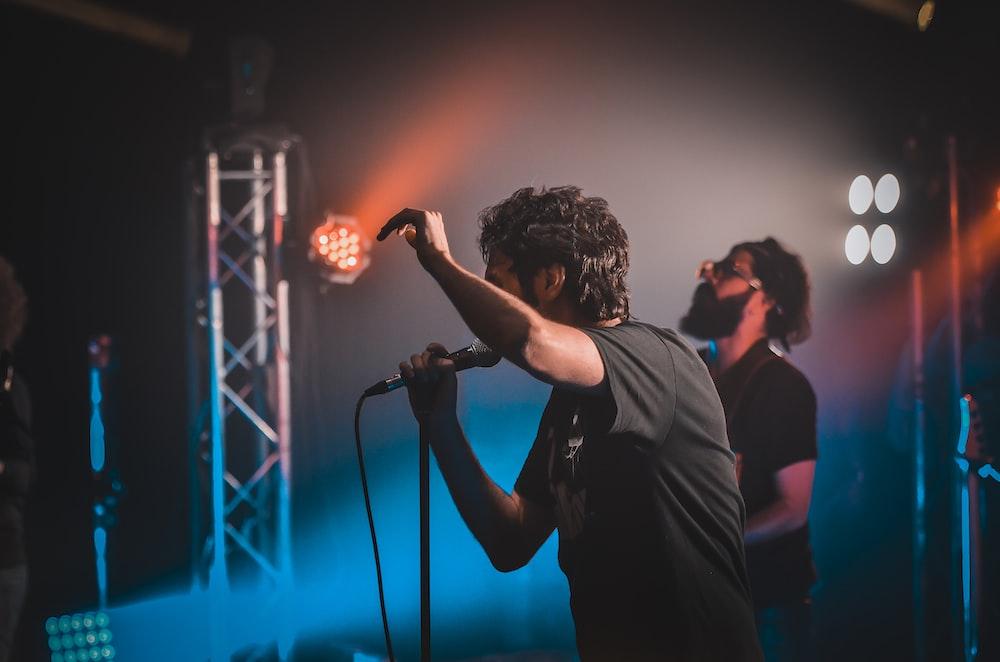 man in black shirt singing on stage