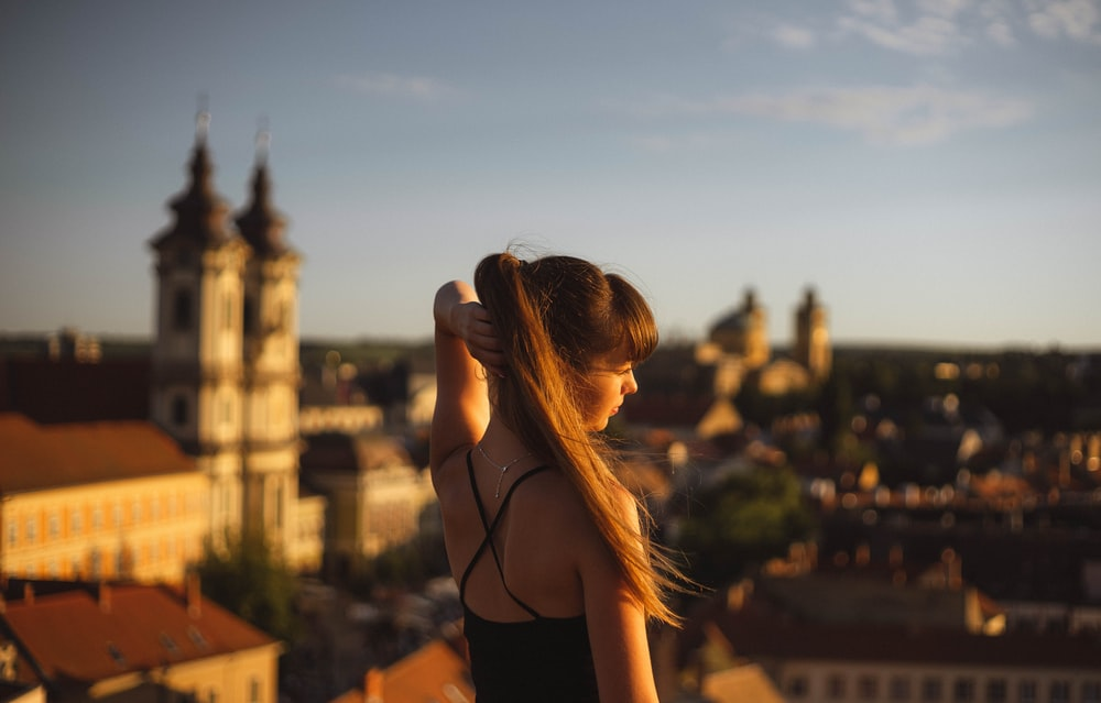 woman in black tank top standing on top of building during sunset