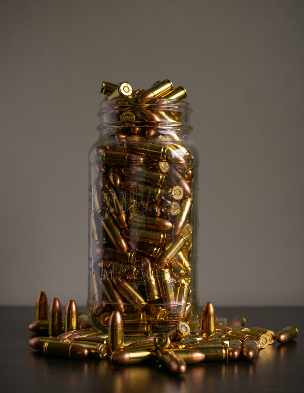 gold and silver coins in clear glass jar
