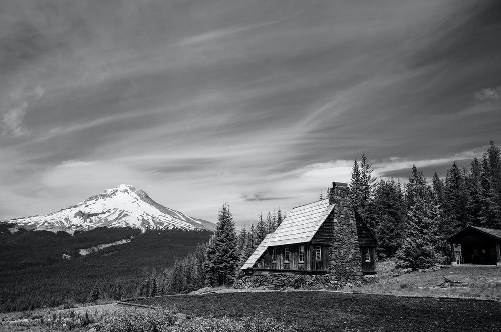 grayscale photo of house near trees and mountain