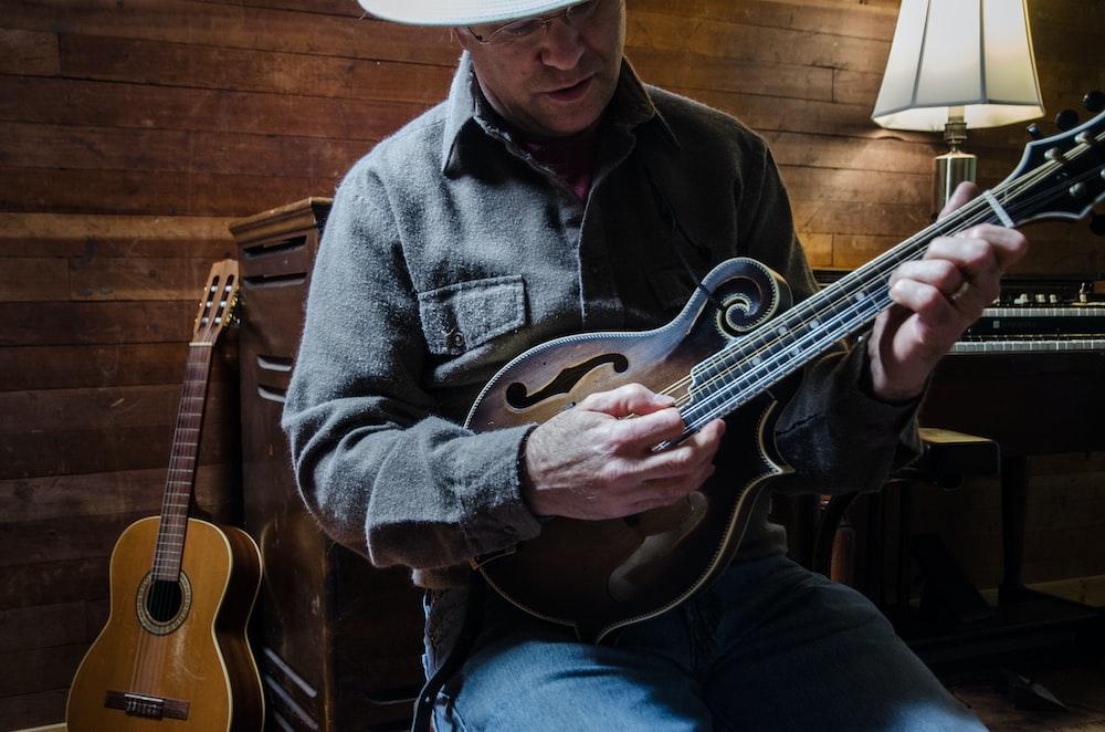man in blue denim jacket playing brown acoustic guitar