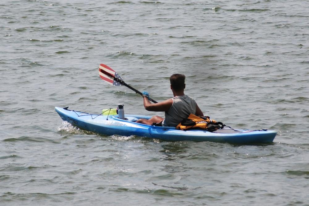 man in orange jacket riding blue kayak on body of water during daytime
