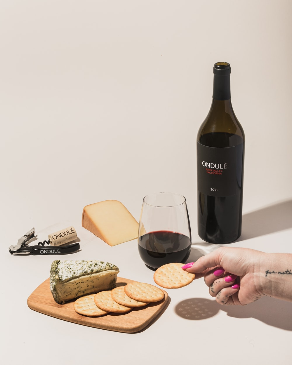 person holding wine bottle pouring on bread and bread