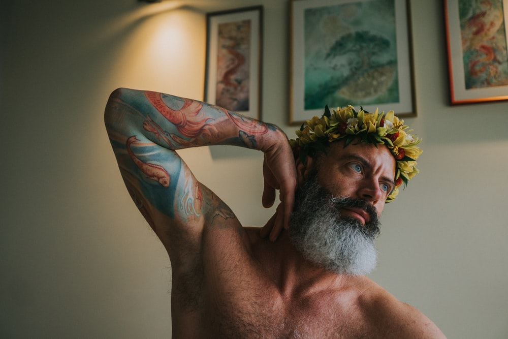 topless man with green and red floral tattoo on his right arm