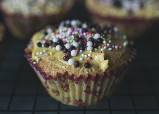 brown and white cupcake with sprinkles on top