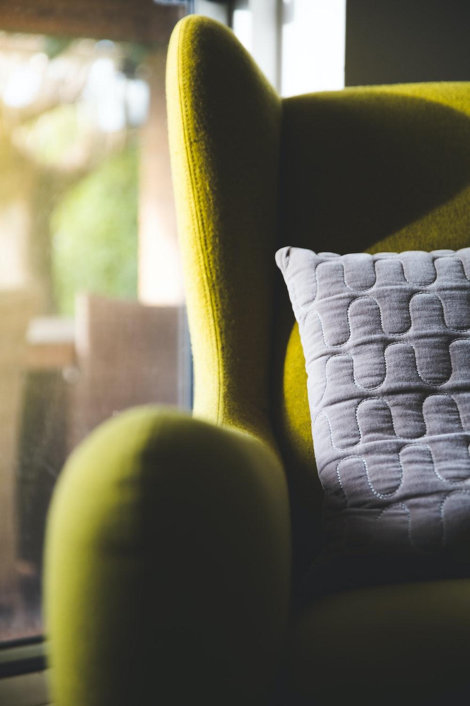 white throw pillow on green sofa