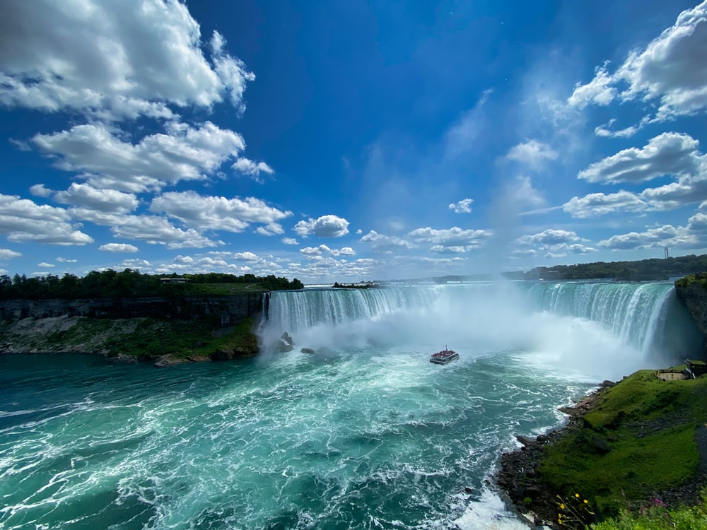 waterfalls under blue sky and white clouds during daytime